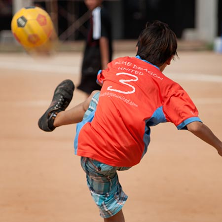 The story of Blue Dragon - Blue Dragon United football club team member, a boy, kicking a ball