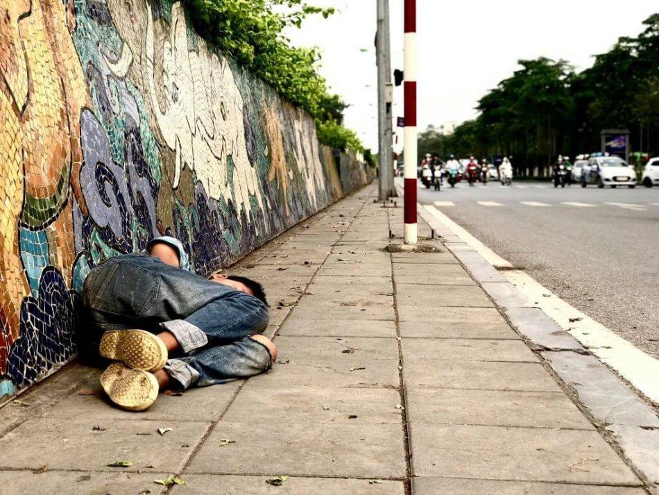 Blue Dragon - street kid sleeping on the sidewalk